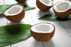 Coconut halves and green leaves. On wooden background stock images