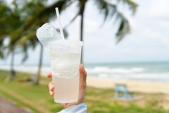 Coconut juice,Drink coconut water in transparent plastic container with beach background - Image stock photos
