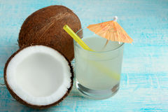 Coconut juice. Halves of coconut with glass of juice with a cocktail straw on a blue wooden background Stock Photos