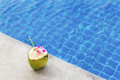 Coconut juice with orchid flower on swimming pool Stock Photo