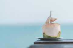 Coconut juice on table in blurred beach background. Coconut juice on wood table in blurred beach background royalty free stock photo