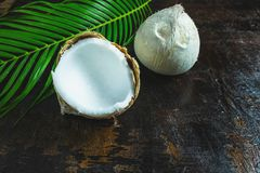 Coconut with leaves on wooden background stock photos