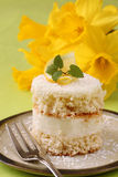 Coconut and lemon cake with daffodils Stock Photography
