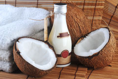 Coconut and massage oil. For body on straw napkin royalty free stock photo
