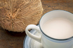 Coconut milk. A cup of coconut milk with a coconut against wood background Royalty Free Stock Photo
