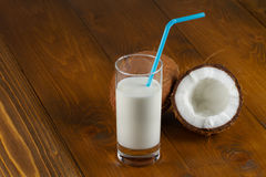 Coconut milk and fresh coconuts on old wooden table Stock Photos