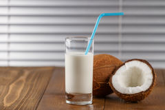 Coconut milk and fresh coconuts on old wooden table Royalty Free Stock Photo