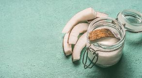 Coconut milk in glass jar with coconut slices on turquoise background. With copy space royalty free stock photography