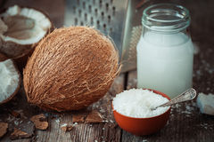 Coconut milk, grounded coconut flakes, coco nut and grater. Coconut milk, grounded coconut flakes, fresh coco nut and grater on background stock photo