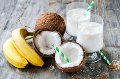 Coconut milk smoothie drink with bananas on wooden background Stock Photography