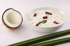 Coconut and Mint chutney served with coconut leaves and raw coconut. Bowl of fresh mint chutney,served with opened  raw coconut and coconut leaves.,selective Royalty Free Stock Image