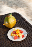 Coconut with mix of different fruit salad on white plate Royalty Free Stock Image