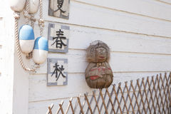 Coconut Monkey on a Wooden Lattice Fence with Line Buoys, and Ja. A vintage mid-century hand carved folk art coconut monkey with a red guitar sits atop a wooden Stock Image