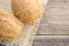 Coconuts  on a rustic background. Coconut nuts, mature, on a rustic jute base on a wooden table Royalty Free Stock Image