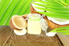 Coconut oil with cut coconut and leaves Royalty Free Stock Photo