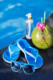 Coconut oil, drink, slippers, sunglasses, pool - summer health holiday concept Stock Photography
