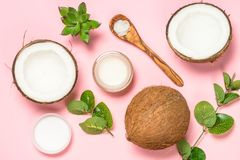Coconut oil, natural cosmetic top view. Coconut oil with fresh cocnut and tropical leaves, natural cosmetic, flat lay image on pink stock image