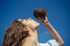 Coconut oil production. Clean eating diet, vegetarian and vegan. Woman is moisturizing her skin with a coconut cream. Drinking beach cocktail. coco milk. woman stock images