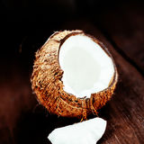 Coconut over dark background. Close up of coco nut on a wooden t Stock Images