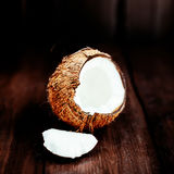 Coconut over dark background. Close up of coco nut on a wooden t Royalty Free Stock Images