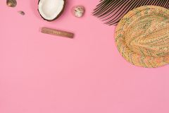 Coconut, palm leaf, hat,  on a pink background. Top view stock photography