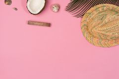 Coconut, palm leaf, hat,  on a pink background. Top view royalty free stock image