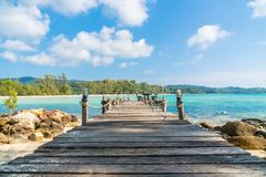 Coconut palm tree on the beach and sea. Beautiful island paradise with bridge and coconut palm tree around sea and beach on white cloud and blue sky - Holiday Stock Image