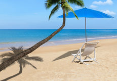 Coconut palm tree with white wooden beach chair and blue parasol on tropical beach Stock Photos