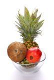 Coconut, pineapple and pomegranate in glass bowl isolated on white Royalty Free Stock Photos