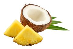 Coconut with pineapple slices and green leaves isolated on white background Stock Photo