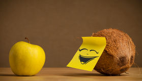 Coconut with post-it note laughing on apple Stock Photography