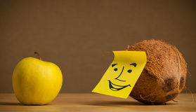Coconut with post-it note smiling at apple Stock Image