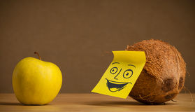 Coconut with post-it note smiling at apple Royalty Free Stock Images