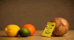 Coconut with post-it note smiling at citrus fruits Stock Images