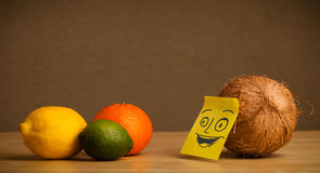 Coconut with post-it note smiling at citrus fruits Royalty Free Stock Photo