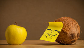 Coconut with post-it note sticking out tongue to apple Royalty Free Stock Photos
