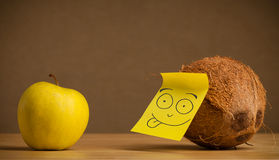 Coconut with post-it note sticking out tongue to apple Stock Images