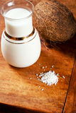 Coconut products and fresh coconut. Coco milk, coconut chips and coconut on a wooden table Royalty Free Stock Images