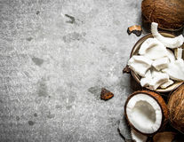 Coconut pulp in a bowl and whole coconuts. Royalty Free Stock Image