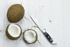 Coconut pulp fresh tropical brown white organic coconut milk knife on wooden white background Royalty Free Stock Images