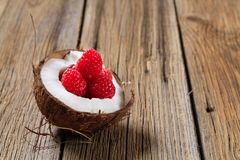 Coconut and raspberries Stock Images