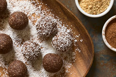 Coconut Rum Balls. Being covered with grated coconut on wooden plate, ingredients (cocoa powder, ground cookies) on the side, photographed overhead with natural Stock Image