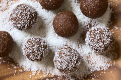 Coconut Rum Balls. Being covered with grated coconut on wooden plate, photographed overhead with natural light (Selective Focus, Focus on the top of the balls Stock Images
