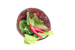 Coconut shell with chillies and vegetables Stock Photos
