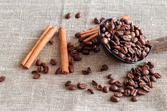Coconut shell with coffee beans, anise and sticks cinnamon. Sack Royalty Free Stock Photo