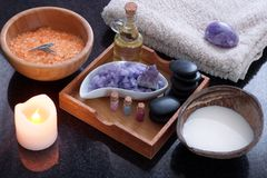 A coconut shell with milk alongside a spa treatment set with orange bath salt, purple massage salt, hot stones, aromatic Stock Photography