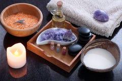 A coconut shell with milk alongside a spa treatment set with orange bath salt, purple massage salt, hot stones, aromatic. Oil and soft towels Stock Photography