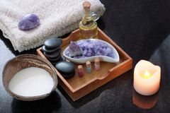 A coconut shell with milk alongside a spa treatment set with purple salt, hot aromatic oil stones and soft towels. Royalty Free Stock Photography