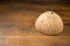 Coconut shell upside down on a wooden background stock photo