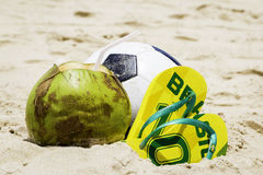 Coconut, Soccer ball and Flip flop with Brazil sign on the sand Royalty Free Stock Photography
